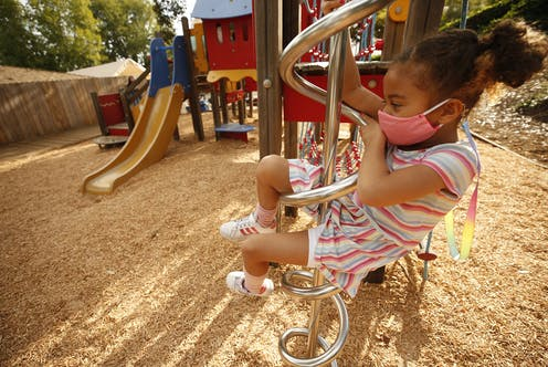 Young girl climbs playground equipment