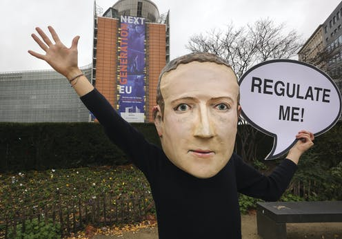 """A campaigner from the global citizens movement Avaaz wearing a mask of Facebook CEO Mark Zuckerberg holds a sign reading """"Regulate me"""" outside the European Commission"""