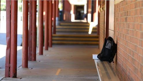 Una mochila sobre un banco en un patio escolar desierto.