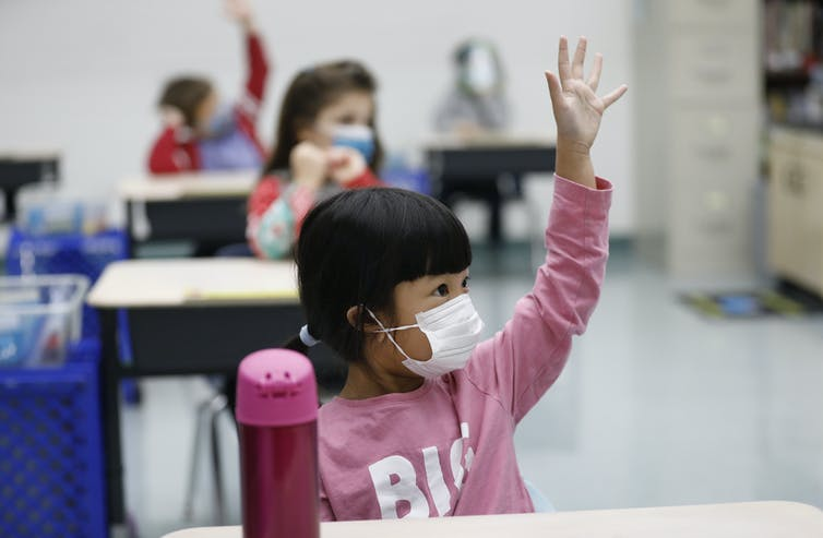 Young girl raises hand in classroom