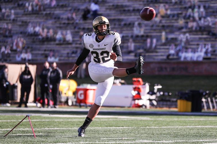 Uniformed football player kicks ball in the air