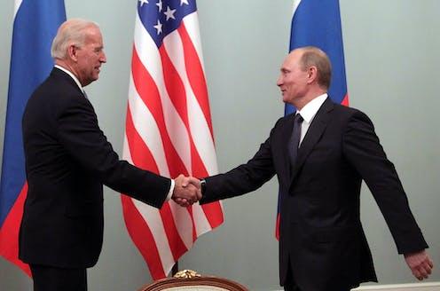 Joe Biden shakes hands with Vladimir Putin.
