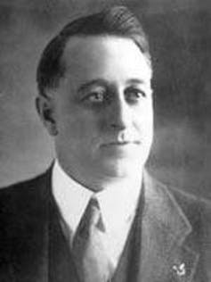 A black and white photo of a man in a suit and tie