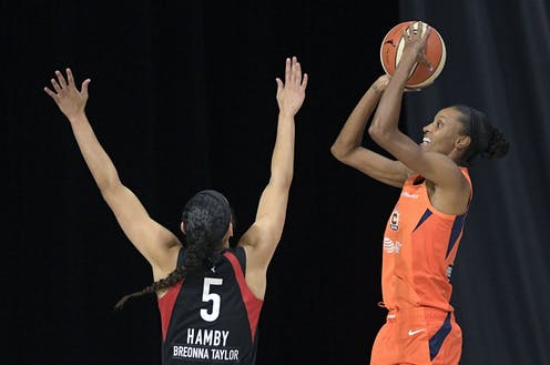 One woman basketball player tries to block another as she takes a shot.