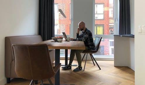 Un hombre habla por teléfono ante un ordenador en la mesa del comedor de una vivienda.