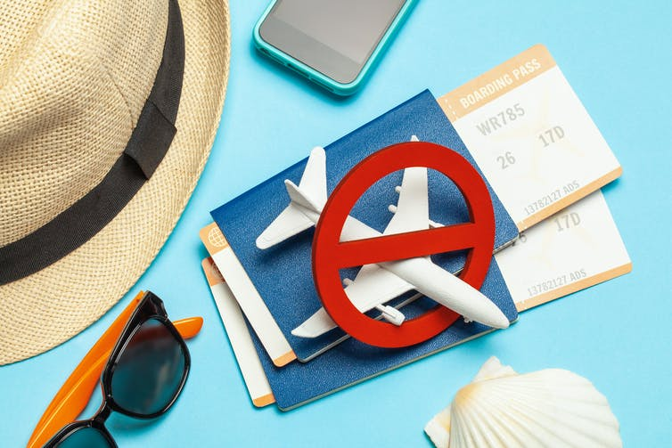 Hat, sunglasses, mobile phone, shell, two passports with boarding passes and a plane figurine with a no symbol over it