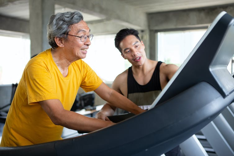 Senior man walking on a treadmill with his young male trainer giving instructions.