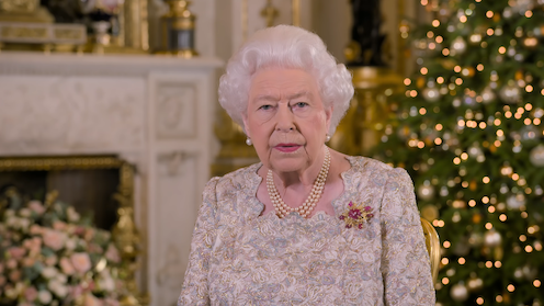 Queen Elizabeth II in a white top in front of a Christmas tree