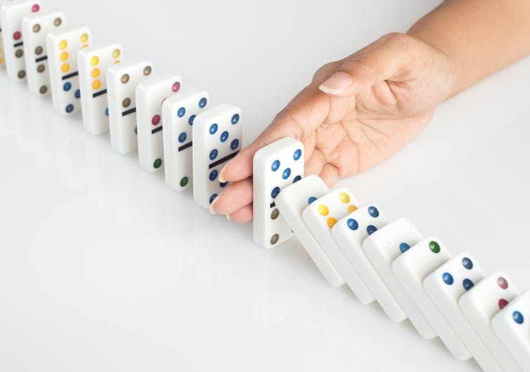 Human hand stopping a line of dominoes from falling. concept image for recovery plan and solution for cascading failures and problems. Dominoes are placed on a white table.