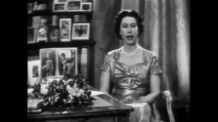 Black and white screenshot of Queen Elizabeth II with framed photos in the background