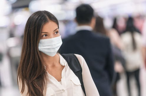 A woman at an airport, wearing a mask