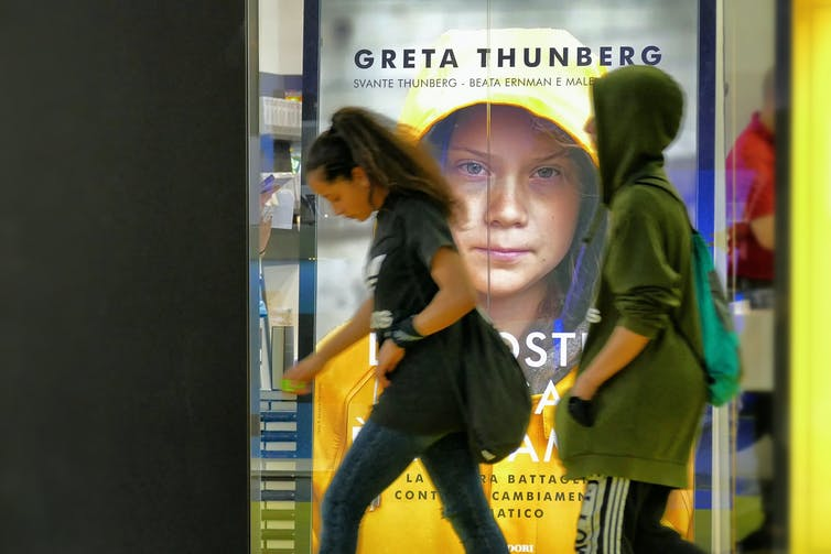 People walking in front of a poster.