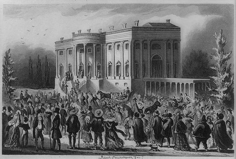 An old picture shows a crowd of people in front of the White House in 1829.