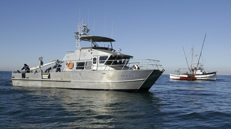 A California game warden boat next to a fishing boat.