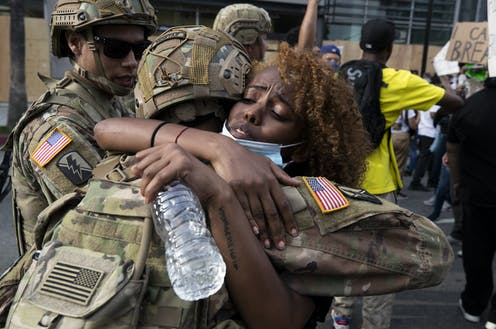 A demonstrator hugs a member of the National Guard during a march in response to George Floyd's death on June 2, 2020 in Los Angeles, California.
