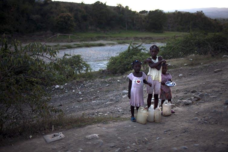 Tres niñas esperan junto a una carretera de tierra en Haití.