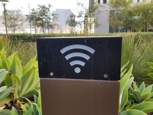 A black box with the Wi-Fi symbol on one side on a brown pedestal amidst plants in a city park