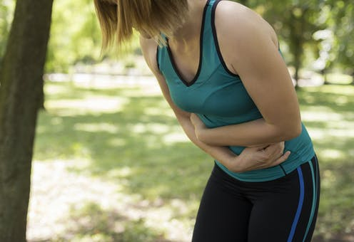 woman in exercise clothes holds belly and leans forward
