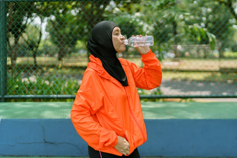 woman in hijab drinks water after sport