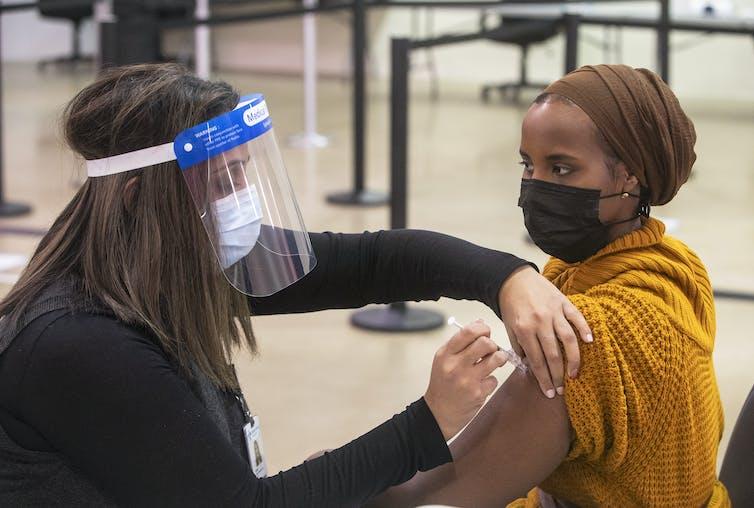 A nurse wearing a face visor vaccinates a woman wearing a face mask.