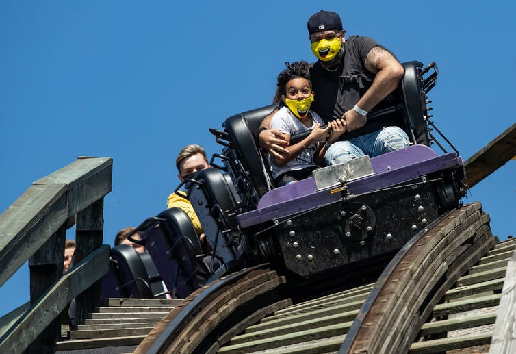A man and child wearing masks ride a roller-coaster.