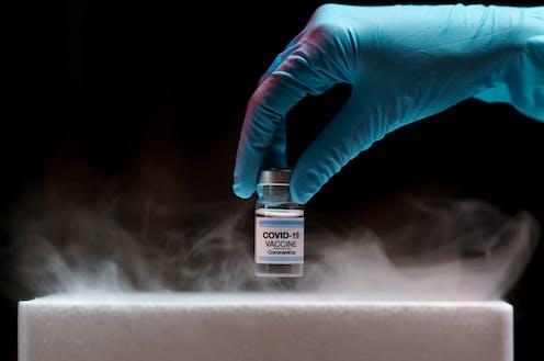 Una mano con guante azul saca un bote de vacuna covid-19 de un receptáculo frigorífico.
