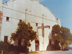 A cavernous white building with a cross attached as a marquee.