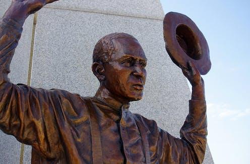 A bronze statue of a black man raising his hands.