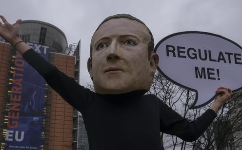 """A person in an oversized mask of Mark Zuckerberg holds up a sign outside the European Commission offices in Brussels in December 2020 with a sign saying """"regulate me"""""""
