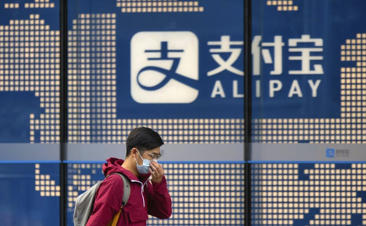 A person in a mask walks past a digital screen of an Alipay sign