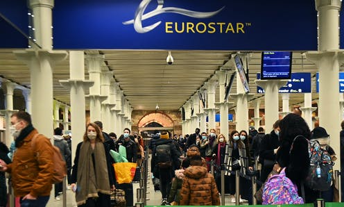 Crowd of wearing face masks at Eurostar entrance in St Pancras International