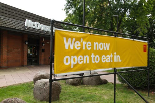 A sign outside McDonalds say the restaurant is open for people to eat inside
