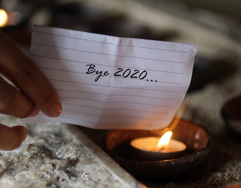 A piece of paper reading 'Bye 2020' held to a flame