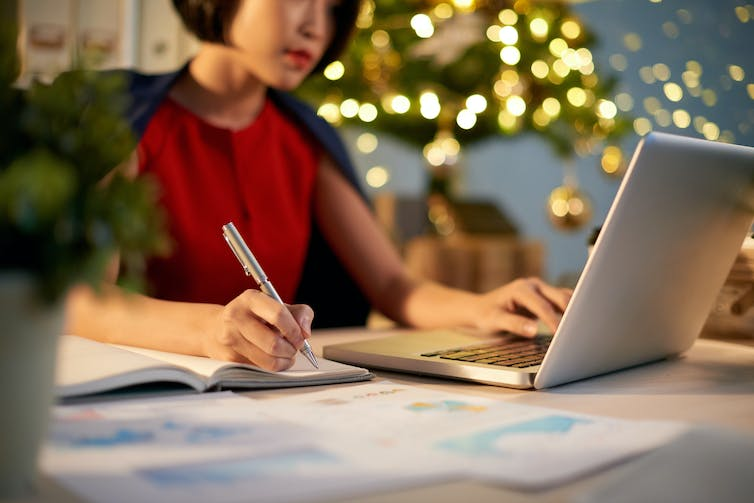 Woman writing in notepad with one hand and typing on laptop with the other in front of Christmas tree