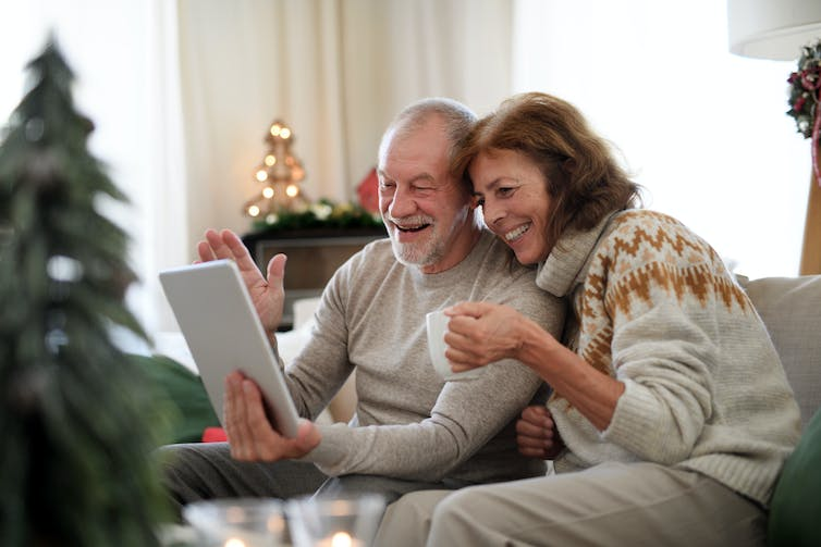 Senior couple smiling during a video call on a laptop with Christmas decorations in the background