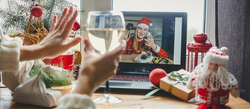 Person raising a glass of wine and waving to a woman wearing a Santa hat and drinking wine on a video call on a laptop