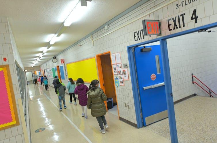 Children walk in single file down a school hallway