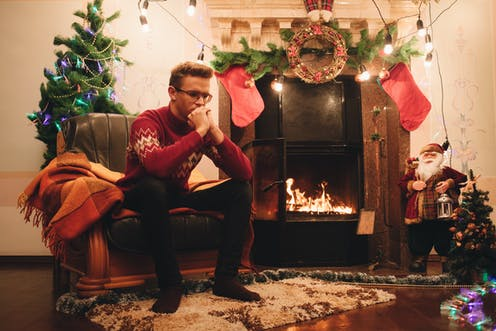 A man sits in a chair next to a fireplace surrounded by Christmas decorations.