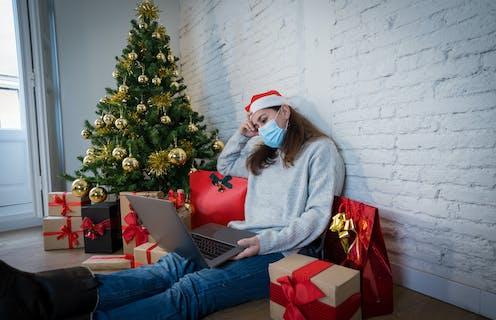 Sad woman alone with computer, mask and christmas tree