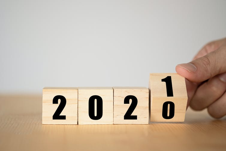 Four wooden blocks spelling out '2020' with the final block flipping from 0 to 1.