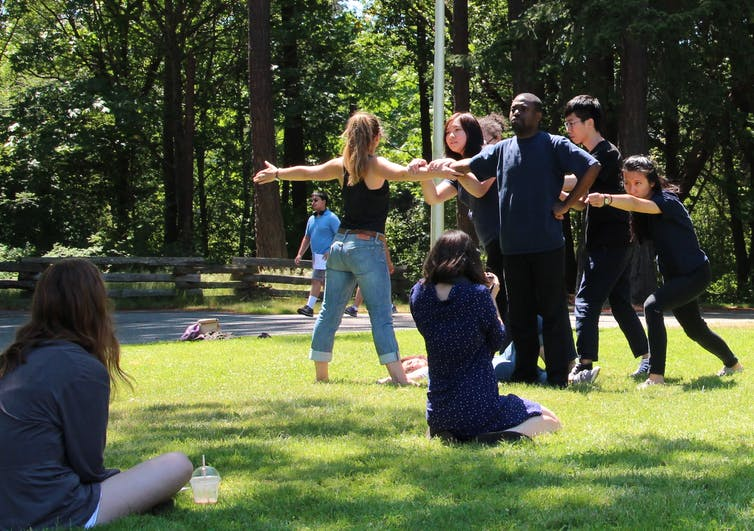 a group of people perform in an outdoor space.