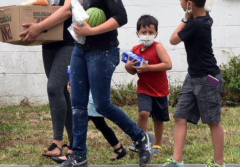 Two boys and two women carry food in a box and in their arms.