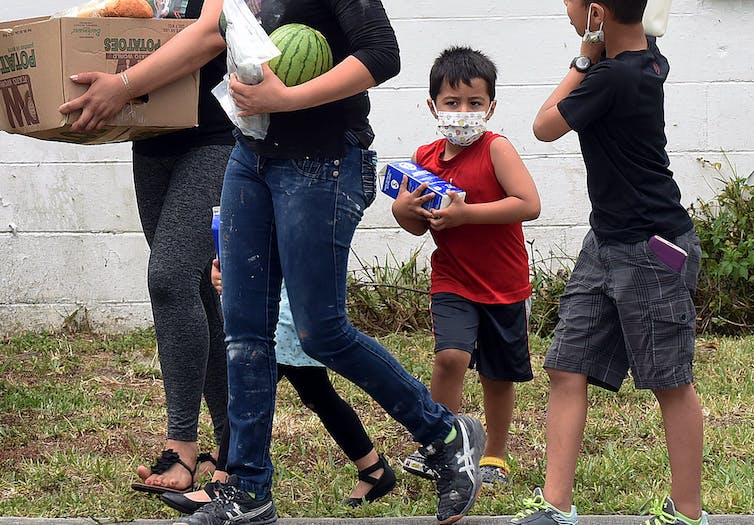 A family walks away carrying groceries in their hands