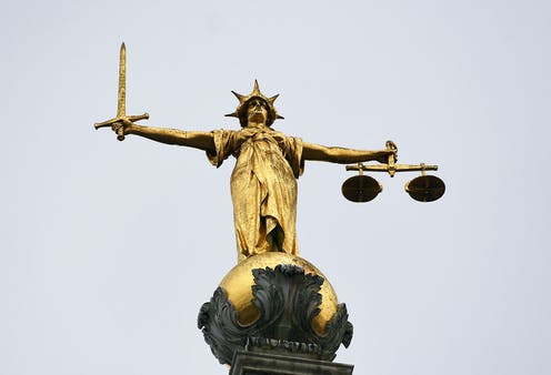 Golden statue of justice holding a sword in one hand and scales in the other