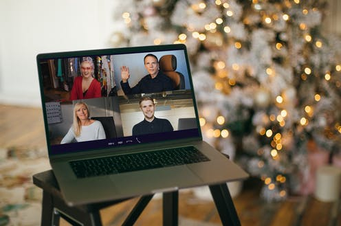 People celebrating Christmas over video conferencing, as shown on the screen of a laptop.