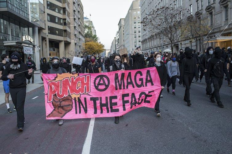 Manifestantes anti-Trump con un cartel que dice 'Golpea a MAGA (Make America Great Again) en la cara' en una marcha en Washington, DC.