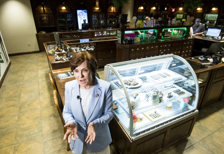 A woman in a blue suit stands in what looks like an upscale diner.