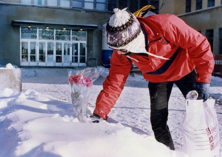 A man in a snow hat and red ski jacket places a bouquet of roses in a snowbank outside a school.