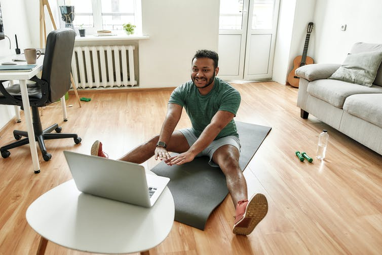 A man on an exercise mat in front of a laptop, with weights and a bottle of water beside him