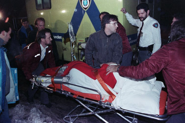 A victim on a stretcher surrounded by paramedics.